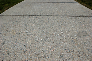 Spalled sidewalk before application of Fusion-Crete concrete resurfacing product.